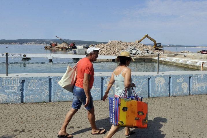 Turisti u Crikvenici promatraju radove na dogradnji i rekonstrukciji Zapadnog lukobrana / Snimio Roni BRMALJ